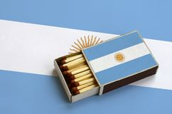 Argentina flag is shown in an open matchbox, which is filled with matches and lies on a large flag.  stock photography
