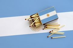 Argentina flag is shown on an open matchbox, from which several matches fall and lies on a large flag.  stock photo
