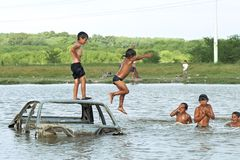 Swimming Argentine children from slum. Argentina, province Buenos Aires, city La Mantanza: in a slum in a suburb children, boys and a girl swim in polluted water stock photography