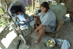 Argentine Mother with child lives in great poverty. Argentina, Province Buenos Aires, city Lanus: in the slum of La Torre, this woman lives with her baby in royalty free stock photo