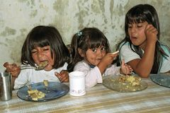 Poor hungry Argentinian girls eat in a soup kitchen. Argentina, province Buenos Aires, city San Isidro the town for rich Argentinians, but also of the second stock photo