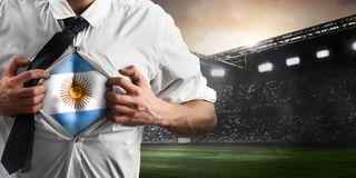 Argentina soccer or football supporter showing flag. Under his business shirt on stadium royalty free stock photography