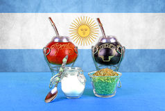 Argentina Yerba. 2 Mate cups with yerba and sugar. The Argentina flag is behind it Royalty Free Stock Images