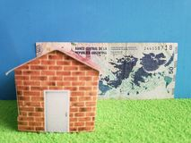 Argentine banknote, figure of a house on green surface and blue background. Backdrop for mortgage and housing value ads, loan for home construction and stock images