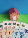 Argentine banknotes, figure of a house on green surface and blue background. Backdrop for mortgage and housing value ads, loan for home construction and stock image