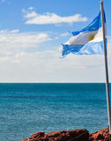 The Argentine flag with the blue sea in the background Stock Photography