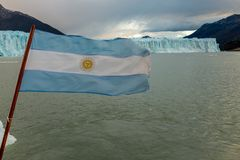 The Argentine flag flutters at the back of a boat in front of the Perito Moreno Glacier in Argentina stock photos