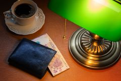 Argentine money, peso, on a stylish desk lit with a banking lamp stock image