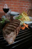 Argentine steak. Juicy Argentine steak with wine and french fries Stock Image