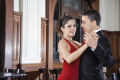 Argentine Tango Dancer With Man Performing Gentle Embrace. Portrait of beautiful female Argentine tango dancer with young men performing gentle embrace in Royalty Free Stock Photos