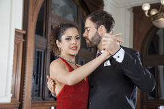 Argentine Tango Dancer Performing Gentle Embrace Step With Partn. Portrait of beautiful female Argentine tango dancer performing gentle embrace step with partner Royalty Free Stock Photography