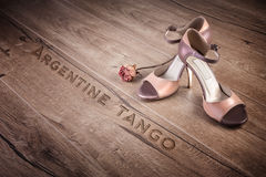 Argentine tango shoes and a dry rose on wood, text Stock Photography