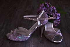 Argentine tango stilettos and lilac flower on dark wood. En floor Stock Photo
