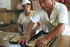 Argentinean bakers bake bread in bakery. Argentina, province of Buenos Aires, city Solano: male and female bakers during their work baking bread and pastries Stock Photo