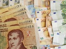 Argentinean banknotes and euro bills of different denominations. European bills of different denominations, background, commerce, exchange, trade, trading stock image