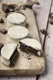 Argentinean-uruguayan alfajores. Some argentinean-uruguayan alfajores filled with dulce de leche and coated with a white coating on a wooden chopping board, on a Stock Photo