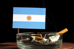 Argentinian flag with burning cigarette in ashtray isolated on black Stock Image
