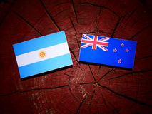 Argentinian flag with New Zealand flag on a tree stump isolated Royalty Free Stock Photos