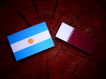 Argentinian flag with Qatari flag on a tree stump isolated. Argentinian flag with Qatari flag on a tree stump Royalty Free Stock Photography