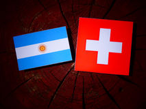 Argentinian flag with Swiss flag on a tree stump  Stock Image