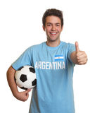 Argentinian soccer fan with ball showing thumb up Royalty Free Stock Image
