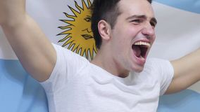 Argentinian Young Man celebrating while holding the Flag of Argentina in Slow Motion. High quality royalty free stock image