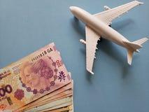 Argentinien-Banknoten, weißes Plastikflugzeug und blauer Hintergrund lizenzfreies stockbild