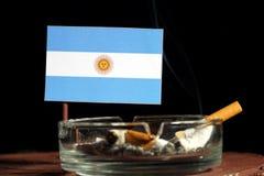 Argentinische Flagge mit brennender Zigarette im Aschenbecher lokalisiert auf Schwarzem Stockbild