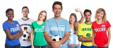 Argentinischer Fußballfan mit Ball und zujubelnde Gruppe anderen Fans Lizenzfreie Stockbilder
