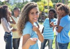 Argentinisches Mädchen mit den Freunden, die auf Kamera zeigen Stockbilder