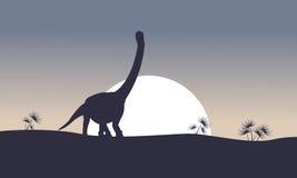 Argentinosaurus sur les silhouettes de paysage de colline Image libre de droits