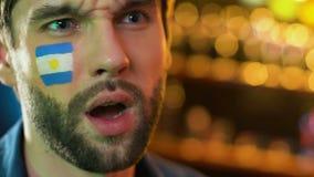 Argentinsk fan som g?r facepalmgesten, rubbning om den f?rlorande leken f?r favorit- lag arkivfilmer