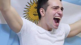 Argentinsk ung man som firar, medan rymma flaggan av Argentina i ultrarapid royaltyfri bild