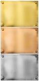 Argento, oro, piatti di metallo bronzei con i ribattini messi Immagini Stock