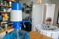 Arger-Flasche Trinkwasser 19 Liter mit blauem Pomp innerhalb der Wohnung mit einem Babyfeldbett im Hintergrund Säubern Sie und Stockfoto
