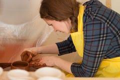 Argila moldando da mulher na roda da cerâmica fazendo o potenciômetro na oficina fotografia de stock royalty free