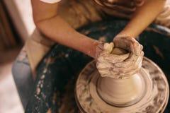 Argila moldando do oleiro na roda da cerâmica imagem de stock