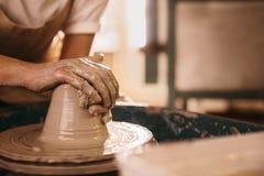 Argila moldando do oleiro na roda da cerâmica fotos de stock
