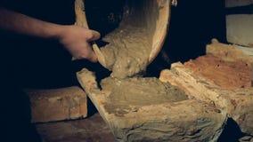A argila molhada derramou da cubeta em um formulário raso vídeos de arquivo