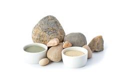 Argile cosmétique bleu et blanc avec des pierres sur un fond blanc Photographie stock