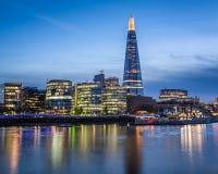 Argine del Tamigi e orizzonte di Londra al tramonto Immagini Stock