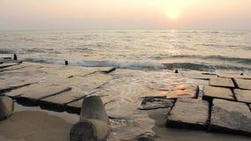 Argine di calcestruzzo e tetrapode che attaccano dal giallo sabbia contro il contesto di spruzzatura delle onde di oceano al di s archivi video
