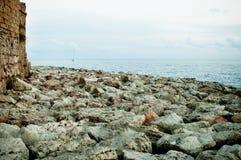 Argine roccioso del mare con gli elementi di una fortezza antica Fotografia Stock Libera da Diritti