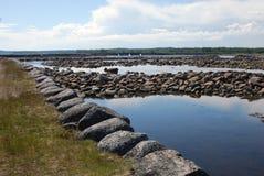 Argini di pietra della diga e di serpantine del mare sui precedenti dei portoni incurvati della diga Fotografie Stock Libere da Diritti