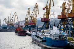 сargo cranes in the port in the winter and boats Royalty Free Stock Image