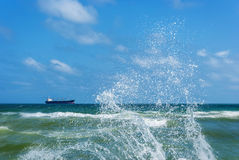 Сargo ship and splashing waves Stock Photos