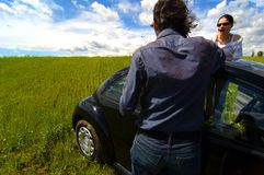 Arguing Couple. A boyfriend and girlfriend argue over their car in a field Stock Photo