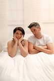 Arguing couple. Arguing brunette couple sitting in bed stock image