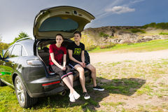 Arguing Couple Sitting on Tailgate of Car by Road Stock Photo