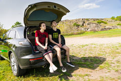 Arguing Couple Sitting on Tailgate of Car by Road Royalty Free Stock Photography